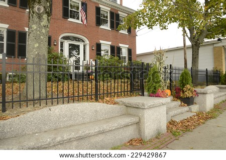 a black wrought iron fence by a red brick colonial style house in autumn.  There is a cement sidewalk and cement bench.   - stock photo