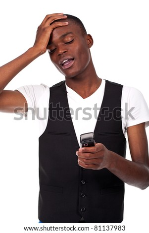 a black young man looking at the phone with a surprised expression - stock photo