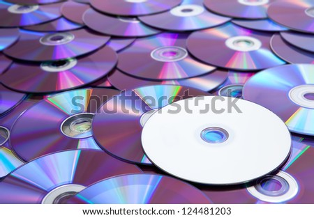 A blank and unlabeld DVD atop a pile of scattered DVDs. - stock photo