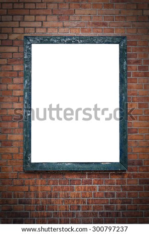 A blank billboard under a spotlight and hanging on a brick wall. - stock photo