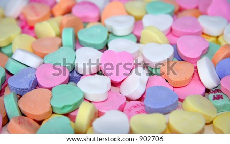 A blank candy heart surrounded by other candy hearts for your message. - stock photo