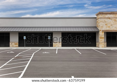 A blank, generic strip mall against a blue sky with an empty parking lot. - stock photo