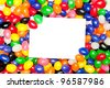 A blank message card in a pile of colorful jellybeans.  Designers can use card to place copy. - stock photo