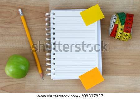 A blank notebook, green apple, pencil, measuring tape on wooden background - stock photo
