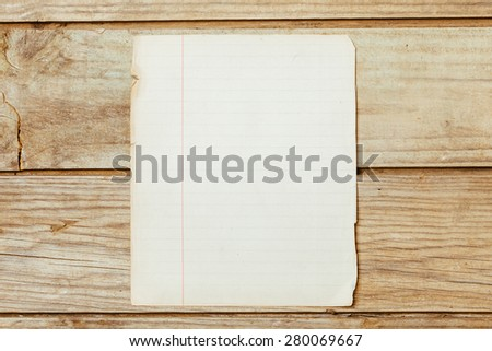 A blank old piece of paper on a wooden desktop. - stock photo
