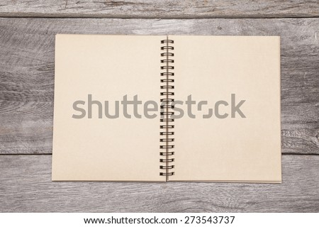 A blank recycled paper scrapbook sits on a rustic wooden background.  - stock photo