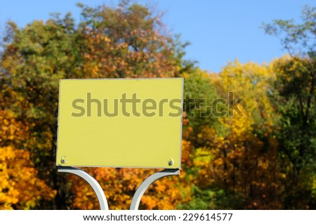 A blank sign plate with bright multicoloured autumn trees  and blue sky in the background - stock photo