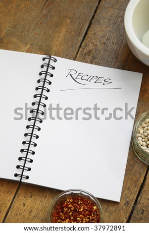 A blank wire spiral bound recipe book with the title 'recipe' hand written at the top of the page. Set on a wooden kitchen table top. Glass dishes of dried chillies and dried white beans also visible. - stock photo