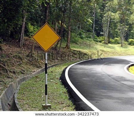 A blank yellow traffic signboard on rural road shoulder.  - stock photo