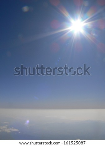 A blanket of clouds in the sky with the sun shining above them. - stock photo