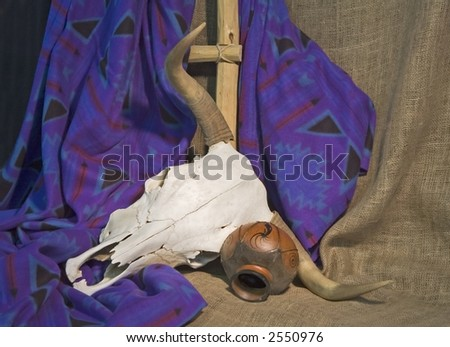 A bleached steer skull with horns, and old pot - stock photo
