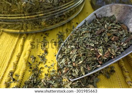 A blend of loose herbal mint tea in a metal scoop. - stock photo