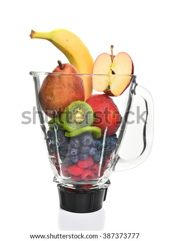 A blender filled with fresh whole fruits for making a smoothie or juice. Healthy eating concept.  - stock photo