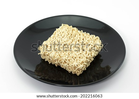 A block of dried Instant noodles on dish with black background - stock photo