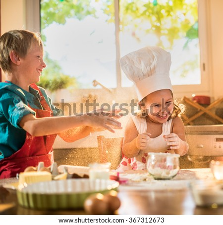 A blond boy and his four year's old little sister are having fun while cooking together in a luminous kitchen. They are standing close to each other at a wooden table, playing with the bowl of flour - stock photo