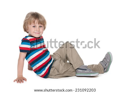A blond boy sits on the floor against the white background - stock photo