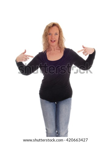 A blond middle age woman in jeans an black sweater pointing with her