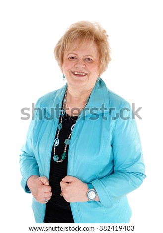 A blond senior woman in a blue jacket, smiling, standing waist up isolated