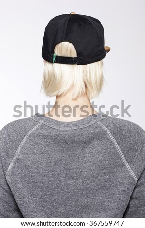 A blond woman(female, girl) wearing black cap and grey shirts back side isolated white at the studio.   - stock photo