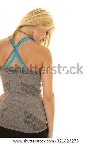 a blond woman in her fitness clothing looking down. - stock photo