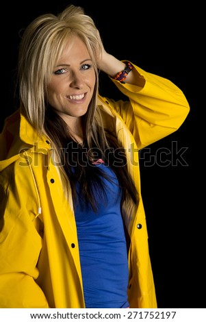 A blond woman in her rain jacket with a smile on her face, playing with her hair. - stock photo