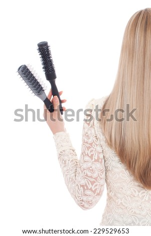 A blond woman on white background holding brushes in her left hand and a hairdryer in her right. She has beautiful, long and healthy hair.  - stock photo