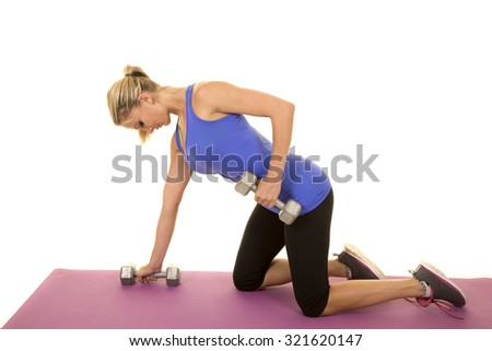 a blond woman working out her arms on her fitness mat. - stock photo