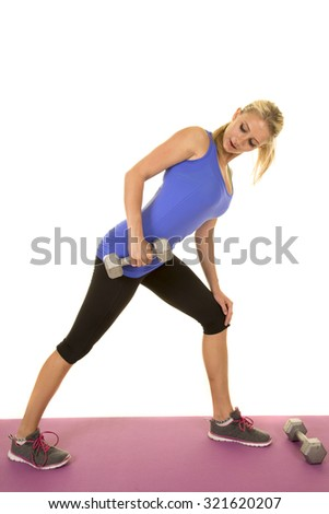 a blond woman working out with weights on a fitness mat. - stock photo