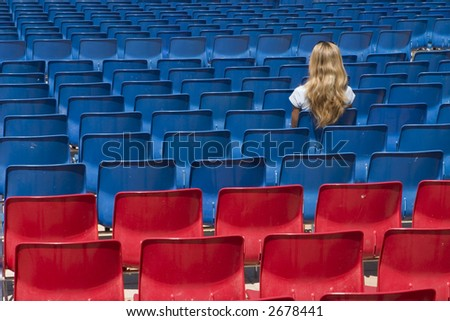 A blond women sitting on a blue chair - stock photo