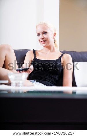 A blonde girl watching TV with the remote control in her hands  - stock photo