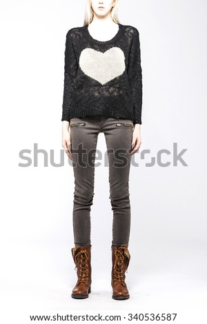 A blonde hair woman(girl, model) stand up wearing grey sweater with heart(love) and blue denim jean(pants, trousers) with hair front side view isolated white. - stock photo