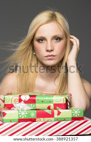 A blonde model holding holiday packages in a studio environment - stock photo