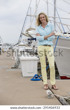 A blonde model posing outdoors with boats - stock photo