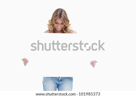 A blonde smiling woman is looking down at a white placard she is holding - stock photo