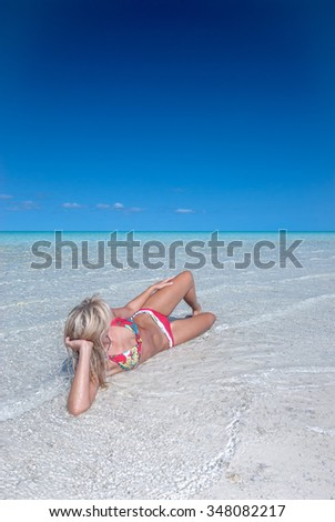 A blonde swimsuit model relaxing in crystal clear waters on an isolated white sand beach - stock photo