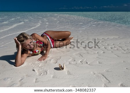 A blonde woman lying on an isolated beach with a singular sea shell - stock photo