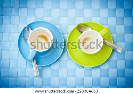 a blue and a green empty cup of coffee - stock photo