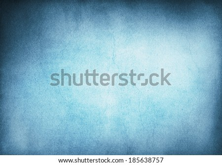 A blue and cyan grunge background with heavy paper textures and a glowing center.  Image has crack patterns and significant grain. - stock photo