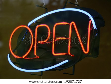A blue and red Open sign in the window of a cafe - stock photo