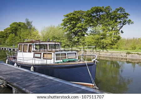 A blue and white boat on the Forth and Clyde Canal near the Falkirk Wheel in Central Scotland, UK. - stock photo