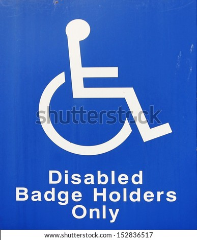 A blue and white sign showing a space reserved for disabled blue badge owners only - stock photo