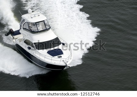 A blue and white speedboat shot from above while travelling fast. - stock photo