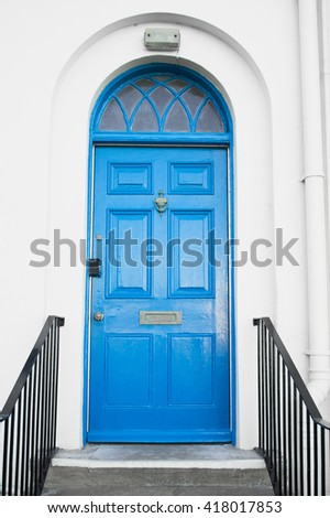 A blue arched door in a white town house - stock photo