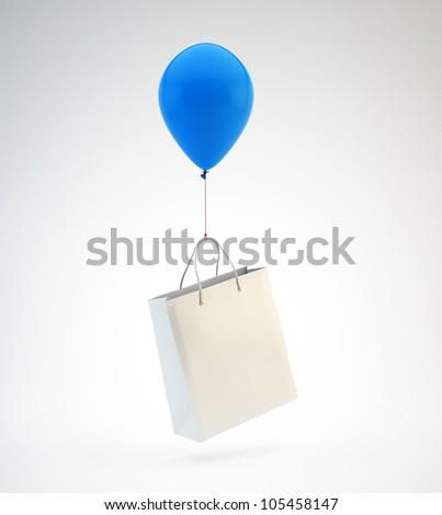 A blue balloon lifting a white shopping bag - stock photo