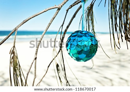 a blue bauble hangs from a tree at the beach - stock photo