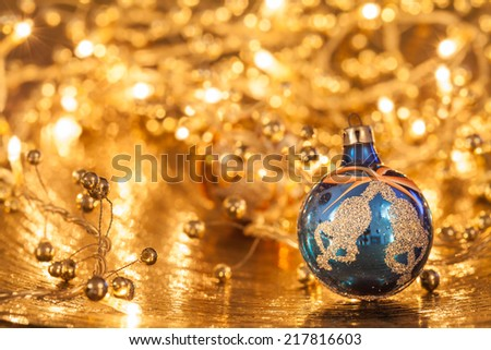 A blue christmas ball on a golden plate - stock photo