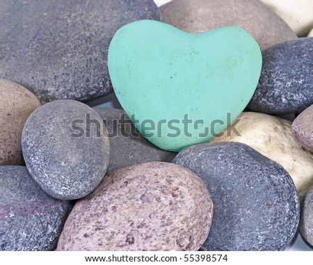 a Blue coloured stone heart surounded by other natural stones - stock photo