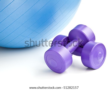 A blue fitness ball and a pair of dumbbells - stock photo