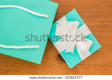 A blue gift box and blue gift bag on a wooden table - stock photo