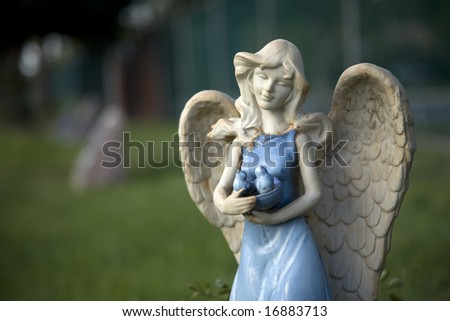 A blue glazed angel protects the garden and those she watches over. - stock photo